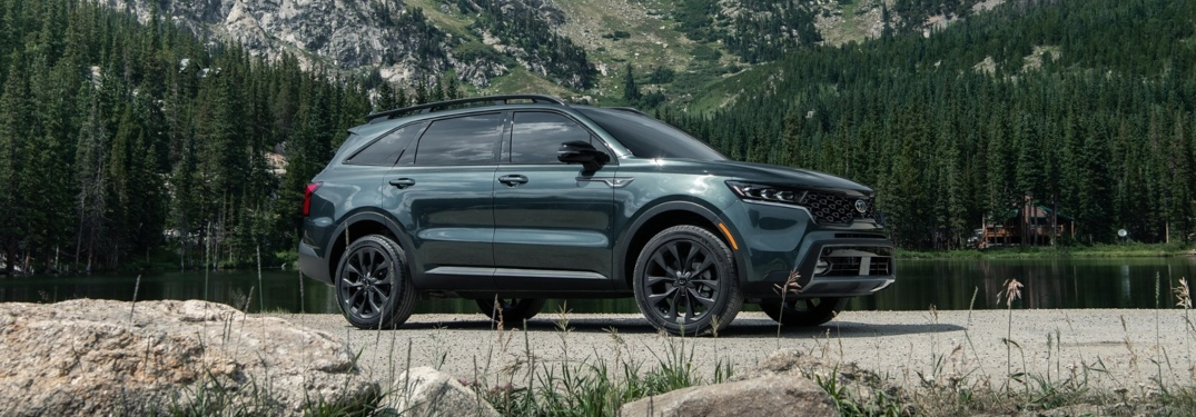 A dark green 2021 Kia Sorento parked in front of a lake and mountains.