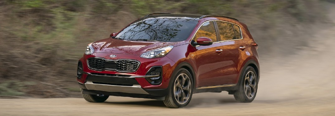 The front and side view of a red 2021 Kia Sportage driving down a road.
