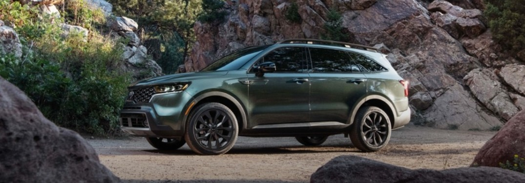 The side view of a dark green 2021 Kia Sorento parked near rocks.
