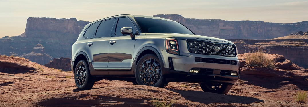 The front and side view of a silver 2021 Kia Telluride parked on a rocky surface.