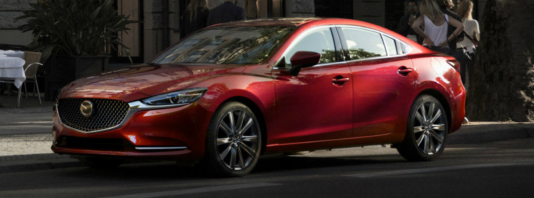 Exterior view of a red 2018 Mazda6 parked curbside in the city