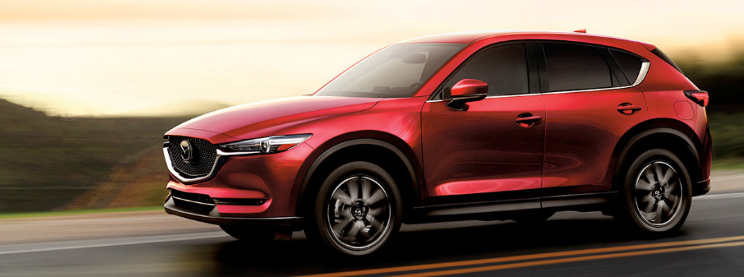 Exterior view of a red 2018 Mazda CX-5 driving down a highway at sunset