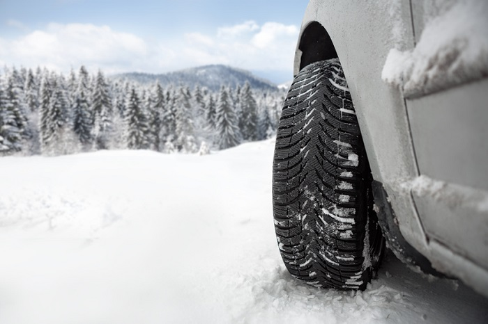 Close-up image of a car tire in the snow.