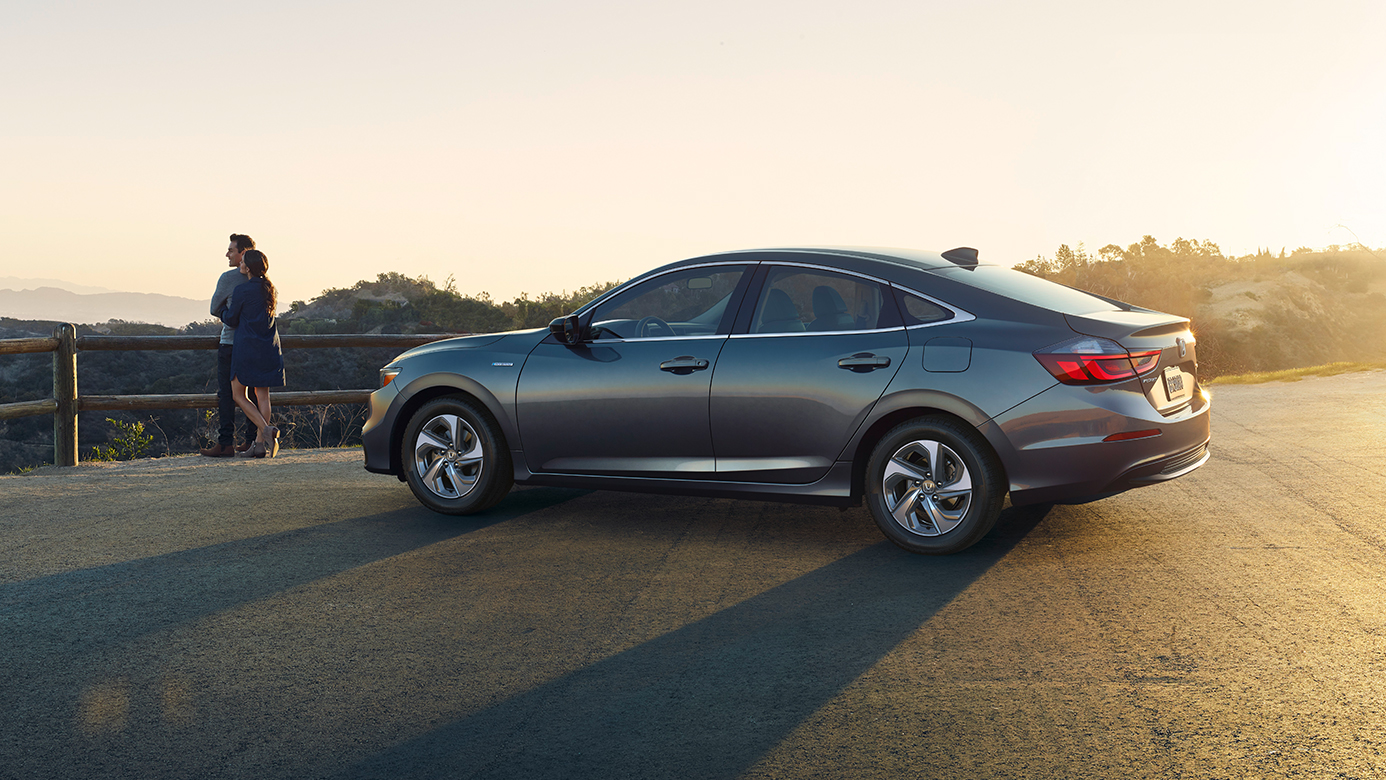 Image of a gray 2019 Honda Insight parked at a lookout point, with a young couple standing in front of it.