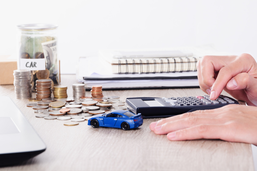 Image of a hand using a calculator and a toy car on the desk.