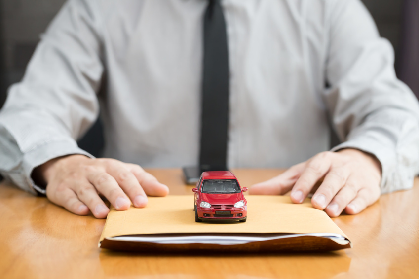 Image of a man in a tie at a desk with a manilla folder and a red toy car.