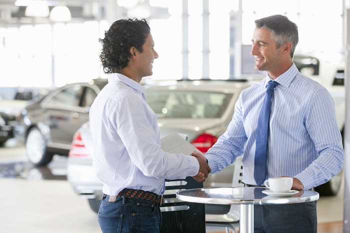 Image of a man and a car salesman shaking hands in a showroom.