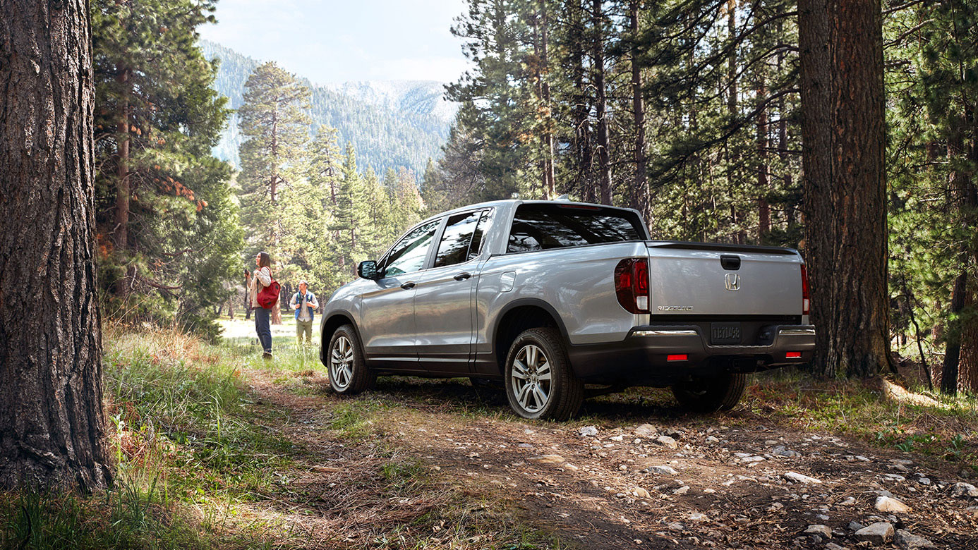 Image of a silver 2019 honda Ridgeline in the woods.