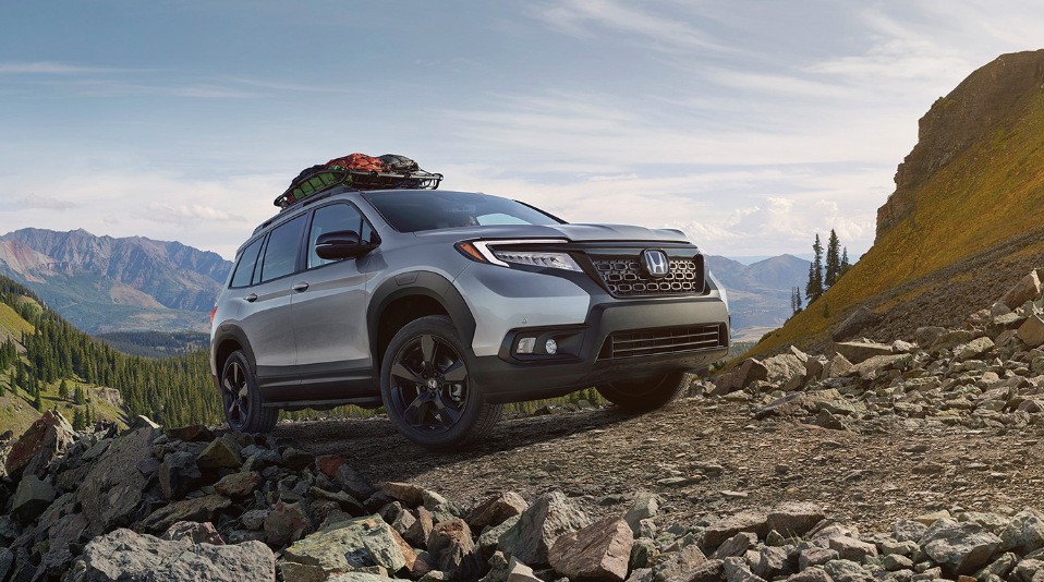 Image of a 2020 Honda Passport SUV driving up a rocky slope.