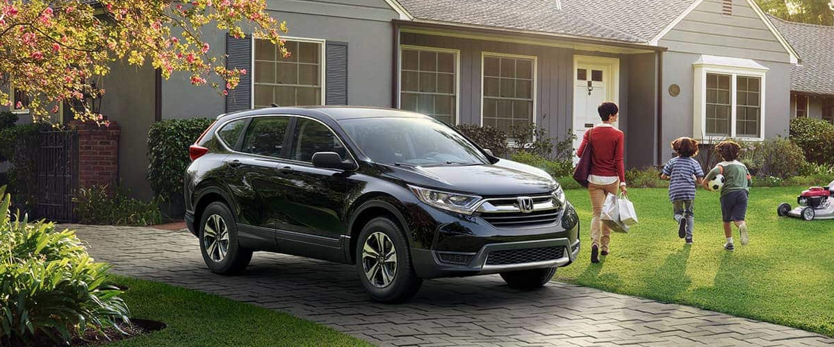 Image of a 2019 Honda CR-V parked in a driveway with a family walking away.