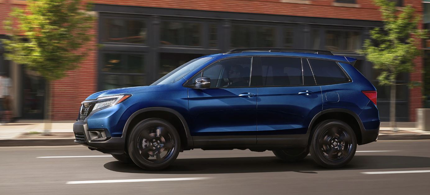 Image of a blue 2019 Honda Passport driving on a city street.