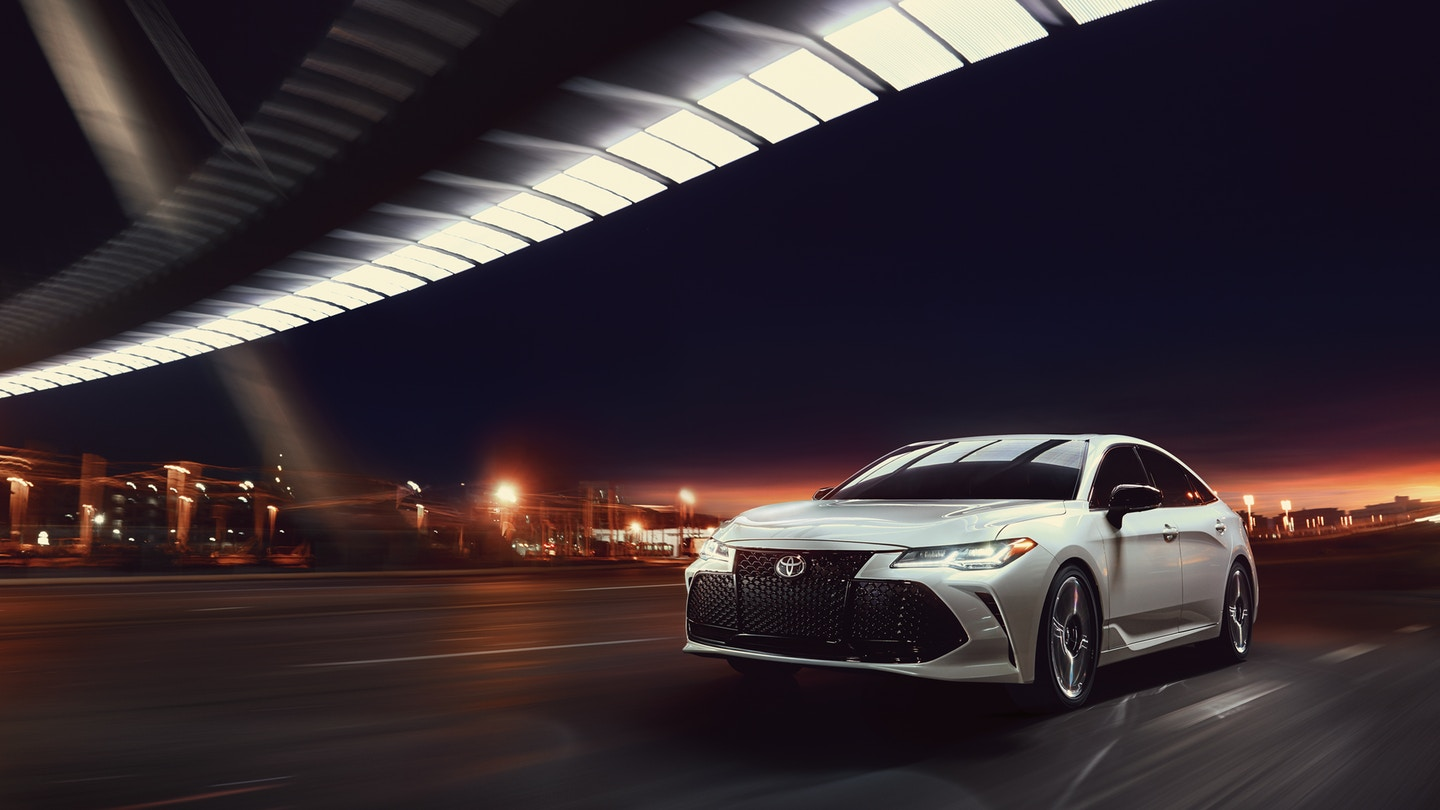Image of a silver 2019 Toyota Avalon driving in the city at night.
