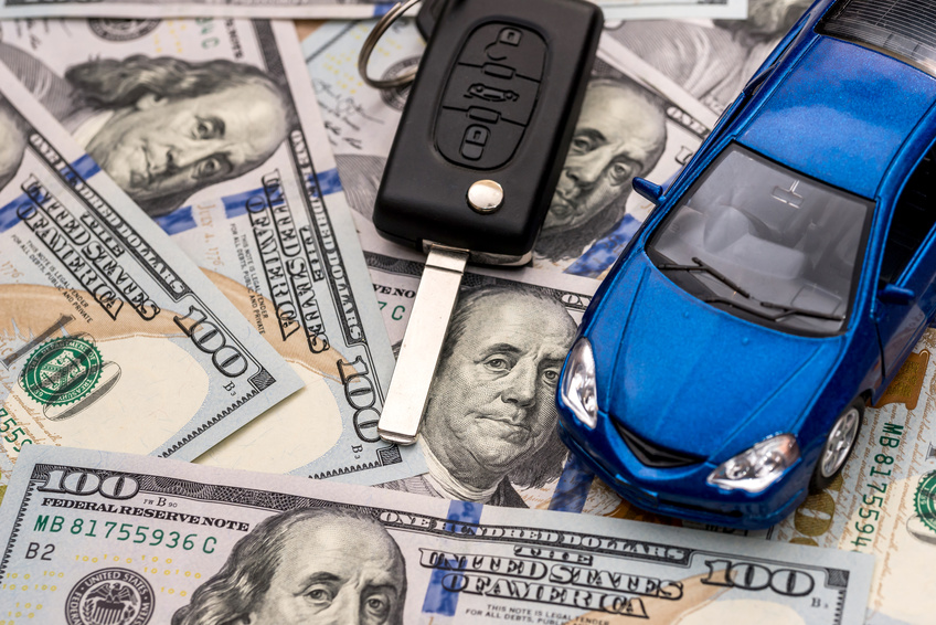 Image of a car key and a blue toy car sitting on $100-dollar bills.