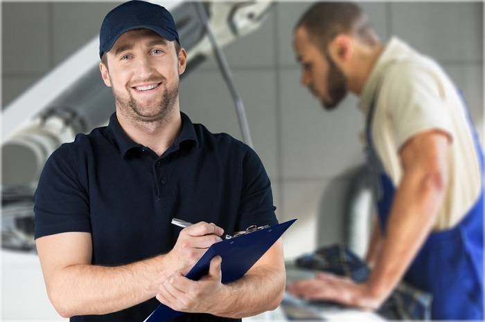 Image of a mechanic holding a clipboard in an auto shop.