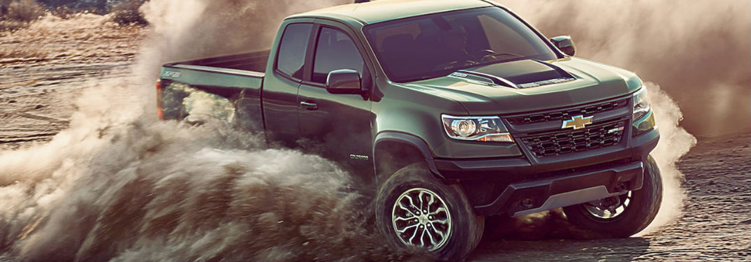 2018 Chevy Colorado driving off-road with dirt flying in the air