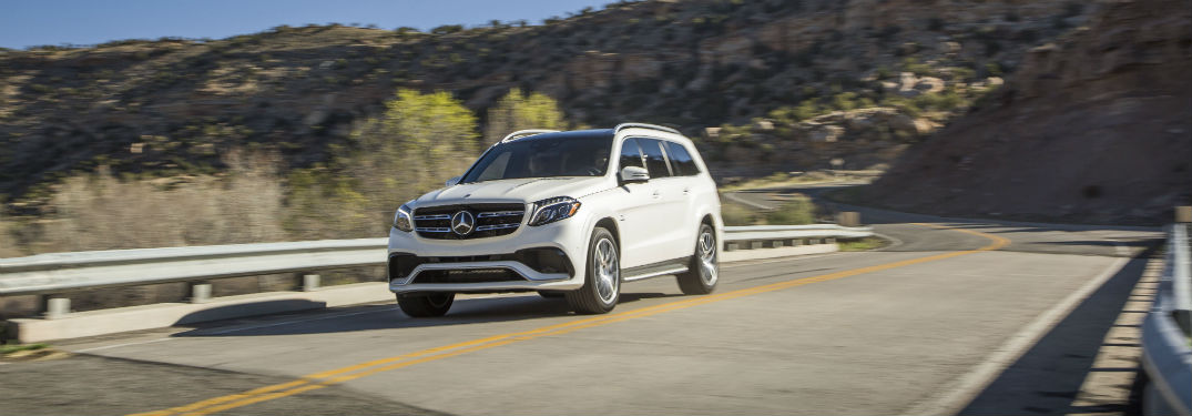 white 2018 Mercedes-Benz GLS SUV driving down a country road