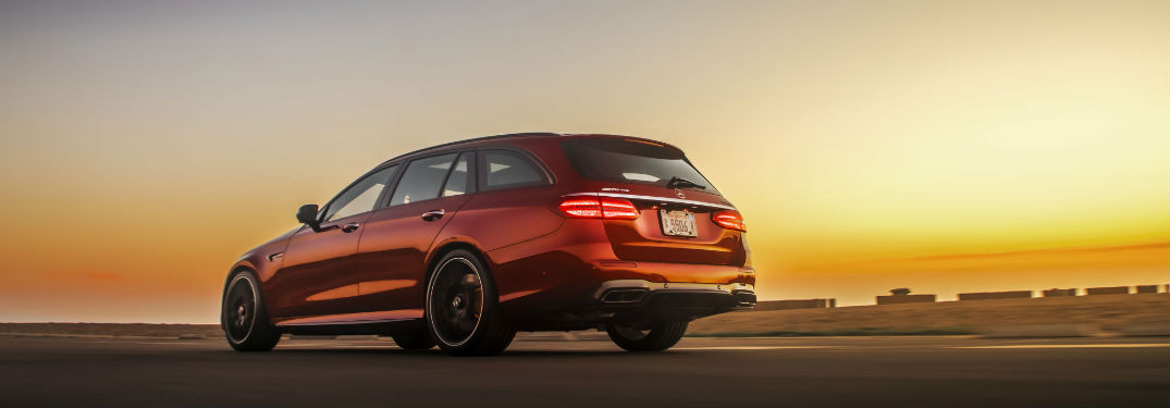 rear view of a red 2018 Mercedes-Benz E-Class Wagon with the sun setting in the background