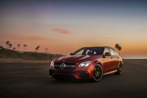 front view of a red-2018 Mercedes-Benz E-Class Wagon with the sun setting in the background