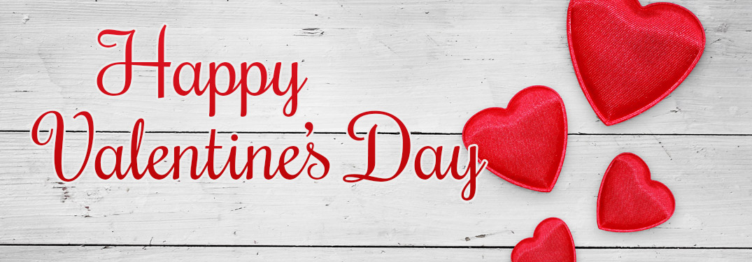 Happy Valentine's Day written in red against a white wood background with red hearts