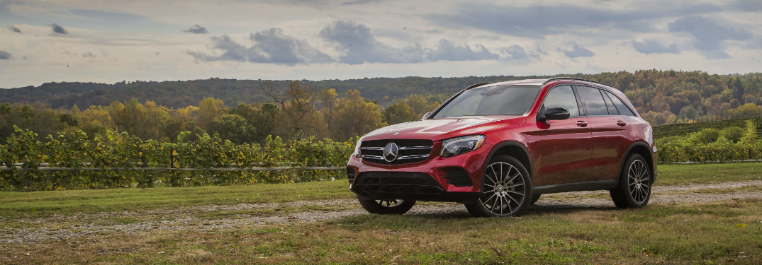 red 2018 mercedes-benz glc 300 suv parked on top of grassy hill overlooking forest