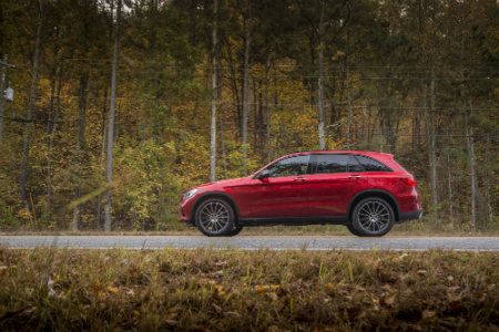red 2018 mercedes-benz glc 300 suv driving on forest road