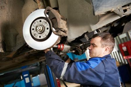 Technician under a car checking brakes