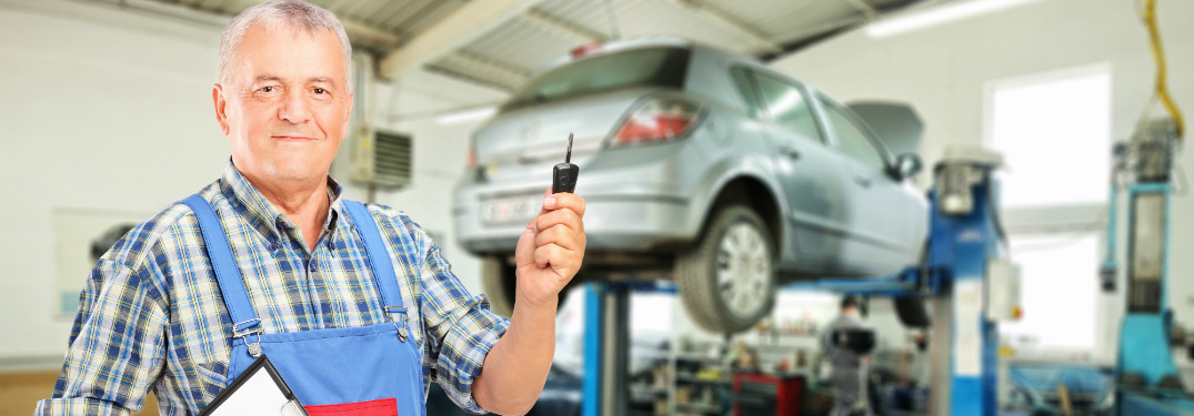 Technician holding car key in front of car in the shop
