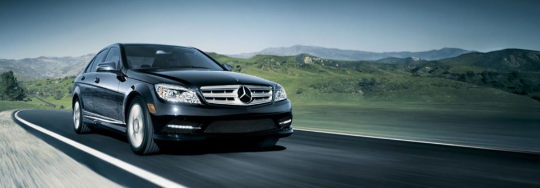 Black Mercedes-Benz vehicle driving along open road