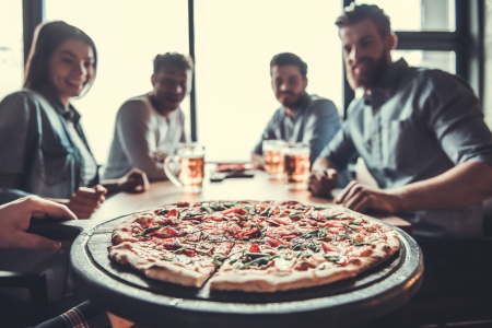 Large pizza  being served to group of friends