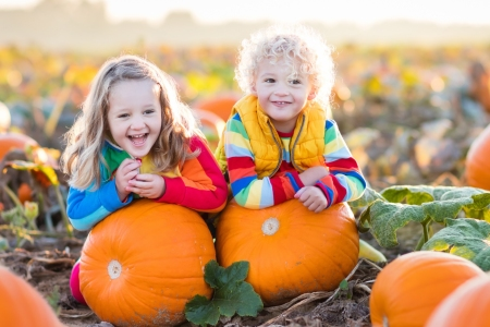 Two girls sitting by pumpkins