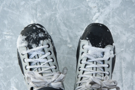 Looking down at hockey skates on ince