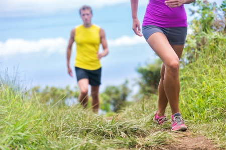 Man and woman running on grassy trail