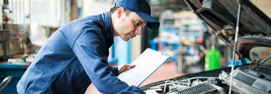 professional mechanic leaning over open hood of car holding clipboard