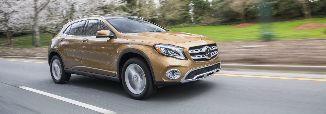 bronze 2018 mercedes-benz gla 250 suv driving on road past trees