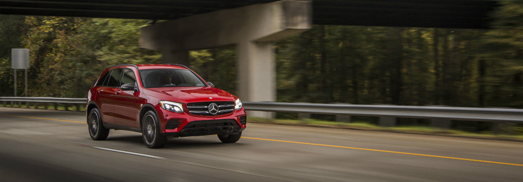 front view of red 2018 mercedes-benz glc 300 driving on empty road underneath bridge