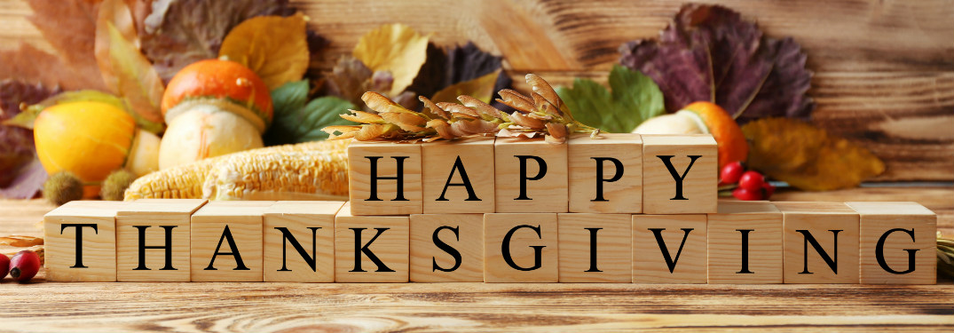 happy thanksgiving written in wooden blocks in front of thanksgiving decorations