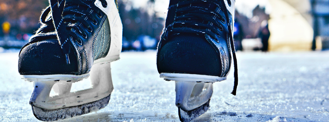 close up of ice skates on ice rink