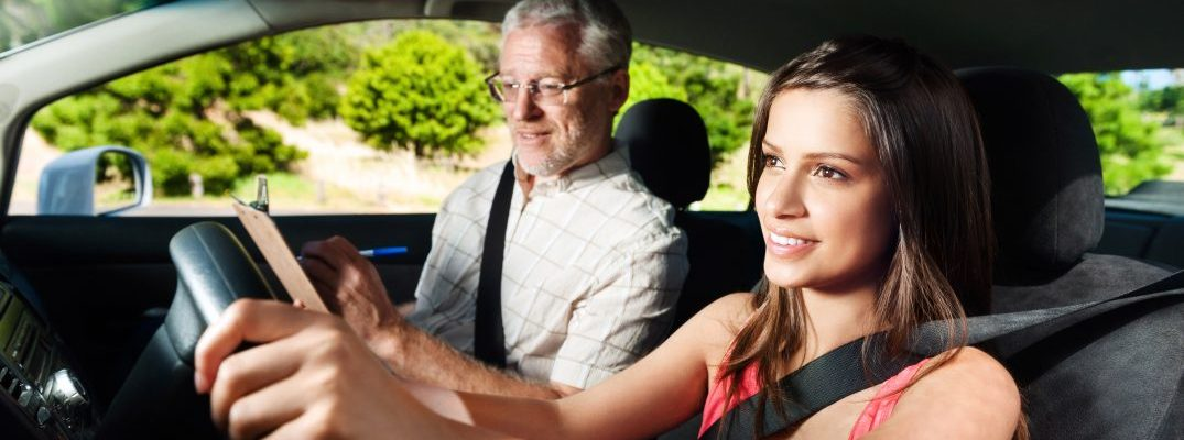 Girl learning to drive with older man in front seat