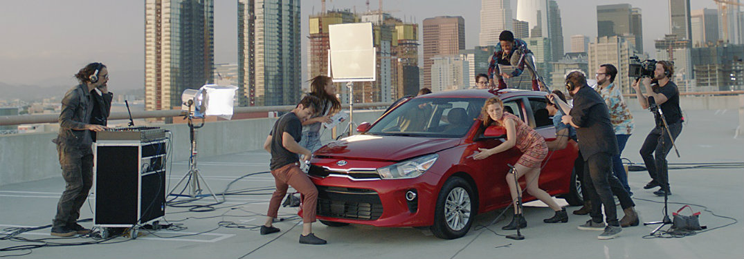 Image from the new 2018 Kia Rio commercial with the Rio being used as an instrument/drum by several performance artists while on too of a skyscraper