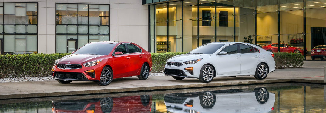 red and white 2019 Kia Forte parked by a stylish pool