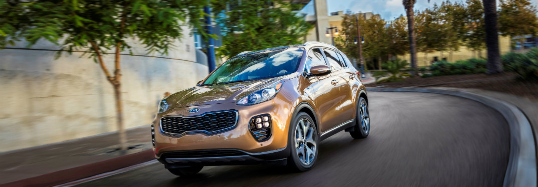 brown 2018 Kia Sportage driving on a curved city road