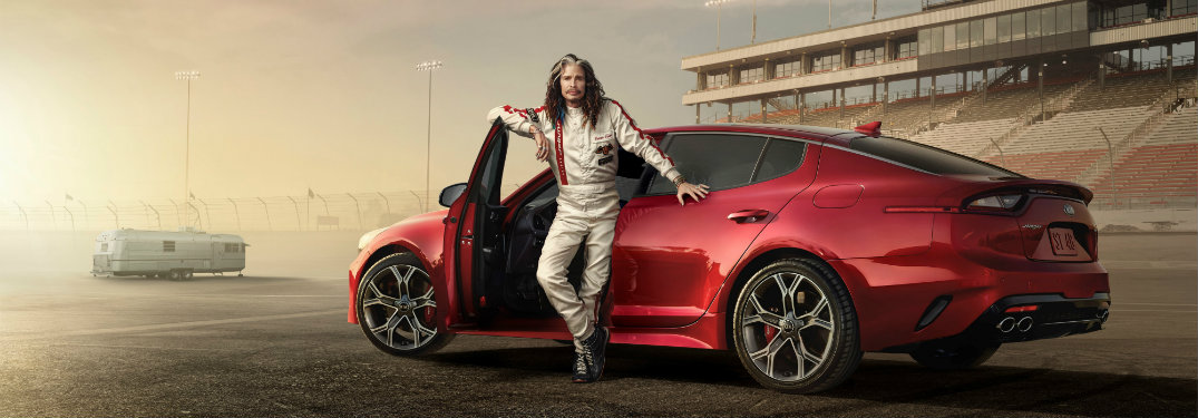 Steven Tyler standing next to the 2018 Kia Stinger in a promo shot for the Kia Super Bowl 52 commercial