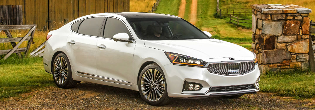 side view of a white 2018 Kia Cadenza parked in front of fields
