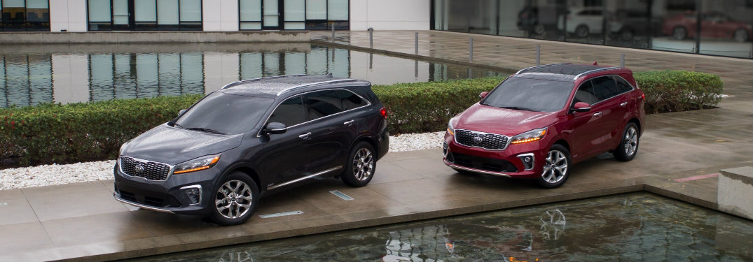 two models of the 2019 Kia Sorento parked by a water feature in front of a nice house