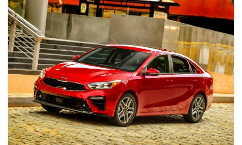 2019 Kia Forte exterior shot with red paint color parked on a stone tiled road next to stair steps