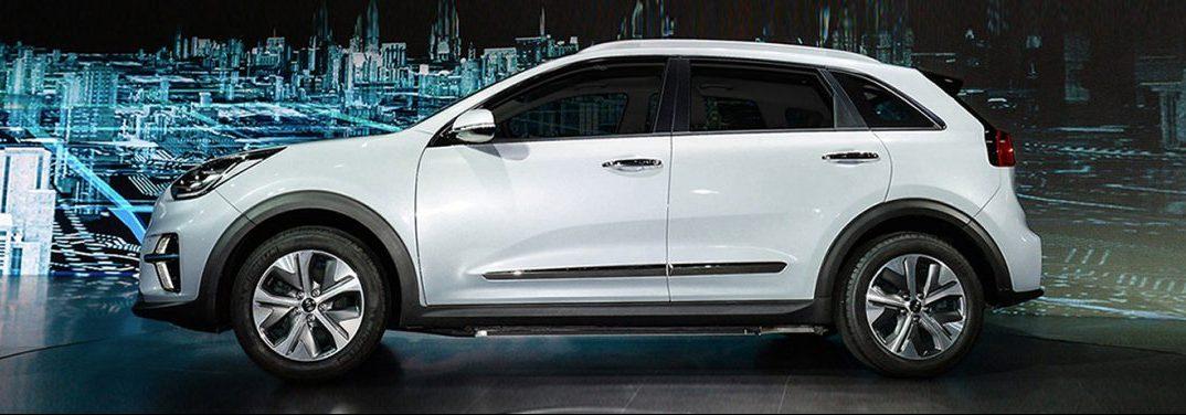 White 2019 KIa Niro EV exterior side view. Charging in a futuristic computerized environment.
