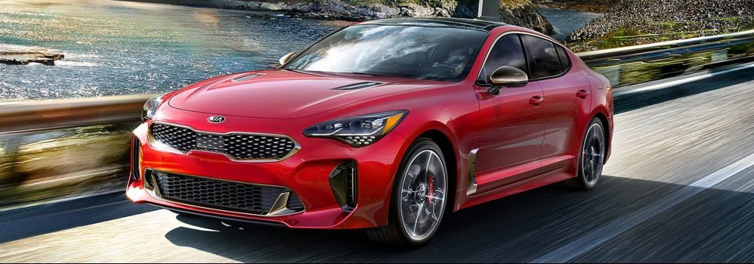 Red 2019 Kia Stinger drives down a highway, front angled exterior view.