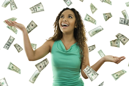 Woman in a green shirt stands in the midst of a falling shower of money on a white background.