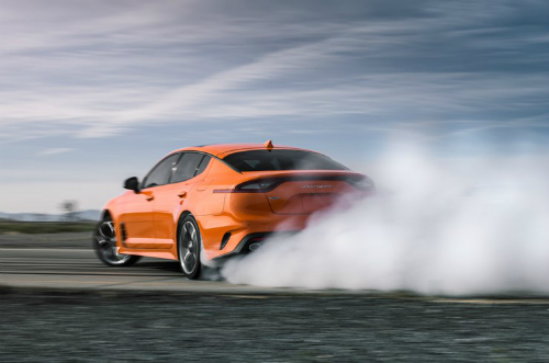 Orange Special Edition 2020 Kia Stinger GTS squeals down a track, with white smoke billowing behind. Rear/side angled view.