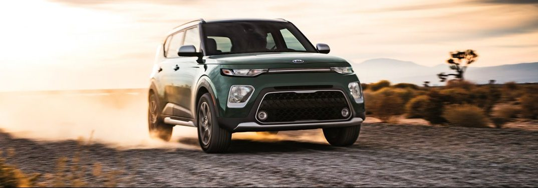 Green 2020 Kia Soul driving down a dusty trail through a desert. Exterior front/side angled view.